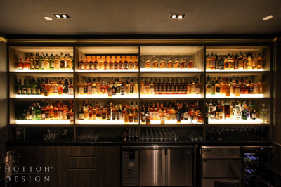 Full rows of whisky collection on the Illuminated tiered bar shelves