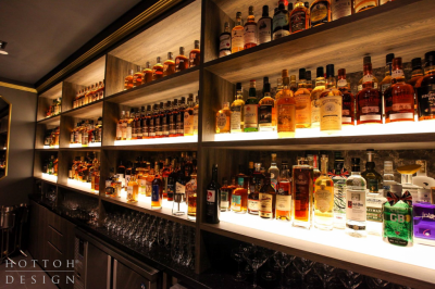 Illuminated tiered bar shelves with the wide collection of whisky