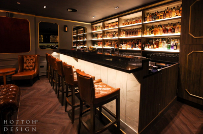 The bar counter with rows of whisky on the illuminated tiered bar shelves