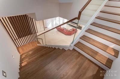 Wooden staircase with glass railing and wooden handrails